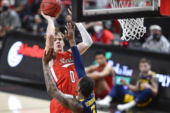 Texas Tech's Mac McClung (0) shoots the ball over West Virginia's Gabe Osabuohien (3) during the first half of an NCAA college basketball game in Lubbock, Texas, Tuesday, Feb. 9, 2021. (AP Photo/Justin Rex)