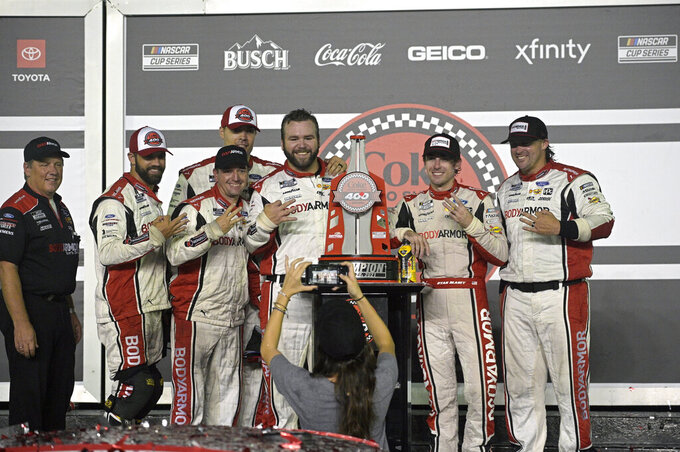 Ryan Blaney, second from right, poses with the champion trophy and crew members in Victory Lane after winning a NASCAR Cup Series auto race at Daytona International Speedway, Saturday, Aug. 28, 2021, in Daytona Beach, Fla. (AP Photo/Phelan M. Ebenhack)
