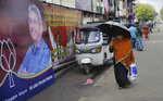 In this Wednesday, Nov. 13, 2019 photo, a Sri Lankan woman walks past election propaganda of presidential candidate and former defense chief Gotabaya Rajapaksa in Colombo, Sri Lanka. Sri Lankans will be voting Saturday, Nov. 16, for a new president after weeks of campaigning that largely focused on national security and religious extremism in the backdrop of the deadly Islamic State-inspired suicide bomb attacks on Easter Sunday. (AP Photo/Eranga Jayawardena)