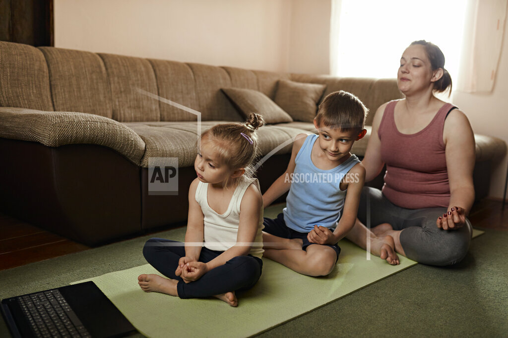 Mother doing yoga with son and daughter while watching online tutorial through laptop