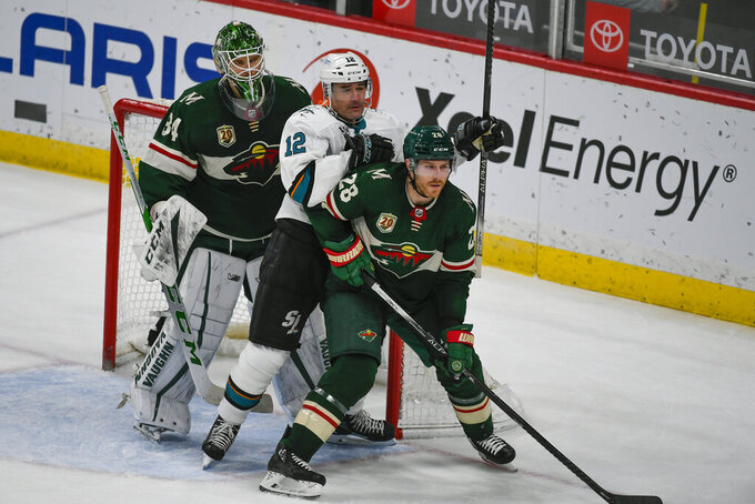San Jose Sharks center Patrick Marleau (12) battles for position with Minnesota Wild defenseman Ian Cole as Wild goalie Kaapo Kahkonen looks on during the third period of an NHL hockey game Saturday, April 17, 2021, in St. Paul, Minn. Marleau has played his 1,767th career game which ties the record with Gordie Howe for the most games played in the NHL. (AP Photo/Craig Lassig)