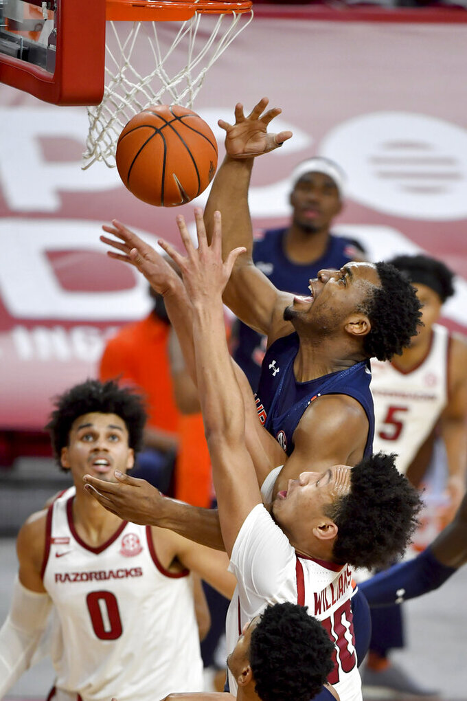 Auburn forward Chris Moore tries to shoot over Arkansas defenders Jaylin Williams (10) and Justin Smith (0) during the second half of an NCAA college basketball game Wednesday, Jan. 20, 2021, in Fayetteville, Ark. (AP Photo/Michael Woods)