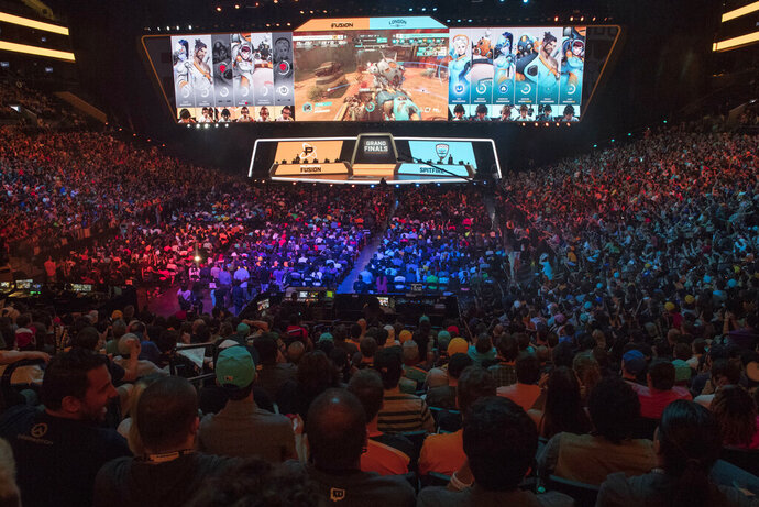 """FILE - In this July 28, 2018, file photo, fans watch the competition between the Philadelphia Fusion and the London Spitfire during the Overwatch League Grand Finals, at Barclays Center in the Brooklyn borough of New York. Overwatch League Commissioner Nate Nanzer is leaving the competitive video game circuit to oversee esports competition for Fortnite publisher Epic Games. Nanzer tweeted Friday night, May 24, 2019, he was moving on from Activision Blizzard, the company behind the Overwatch game and league, for a """"new opportunity."""" He didn't provide further details or a firm timeline except to say he'll be leaving """"soon."""" Epic Games tells ESPN they will hire Nanzer to help turn the world's most popular video game into a viable esport. (AP Photo/Mary Altaffer, File)"""