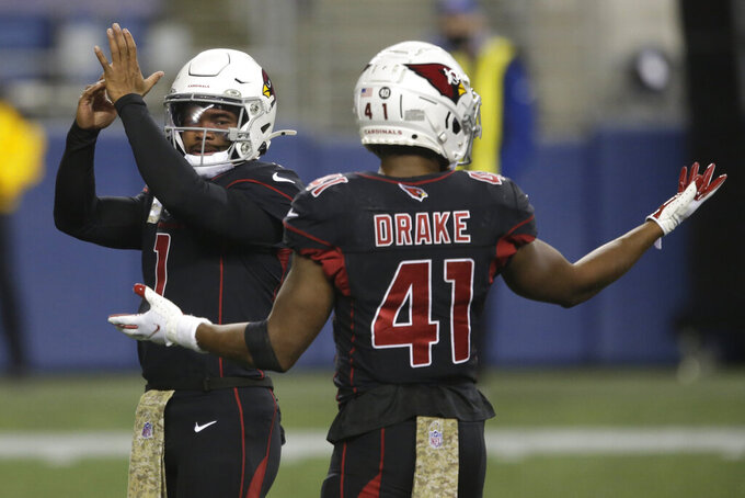 Arizona Cardinals quarterback Kyler Murray, left, calls for a time out as he stands with Arizona Cardinals running back Kenyan Drake (41) during the first half of an NFL football game against the Seattle Seahawks, Thursday, Nov. 19, 2020, in Seattle. (AP Photo/Lindsey Wasson)
