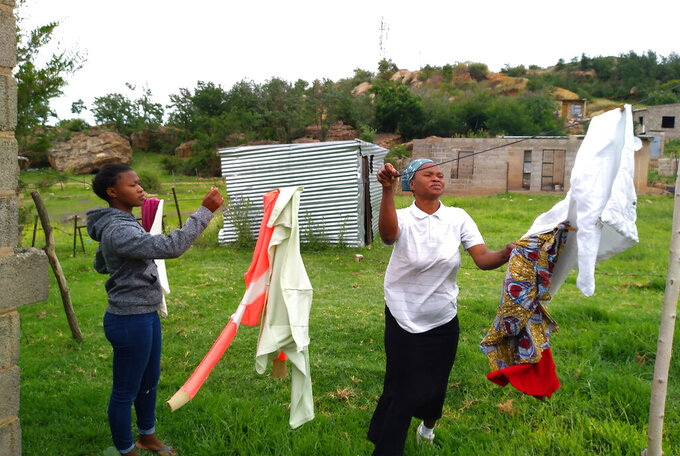 Matefo Litali, 53, hangs laundry with her youngest daughter, Refiloe, 20, whom she regards as her best hope for a better future, in the town of Ha Thetsane, Maseru, Lesotho, on Saturday, Dec. 12, 2020. Litali's dream is to save money to send her daughter to enroll for a hairdressing course, which she believes will enable her to eventually start her own business and be financially independent. (Neo Ntsoma/The Fuller Project via AP)