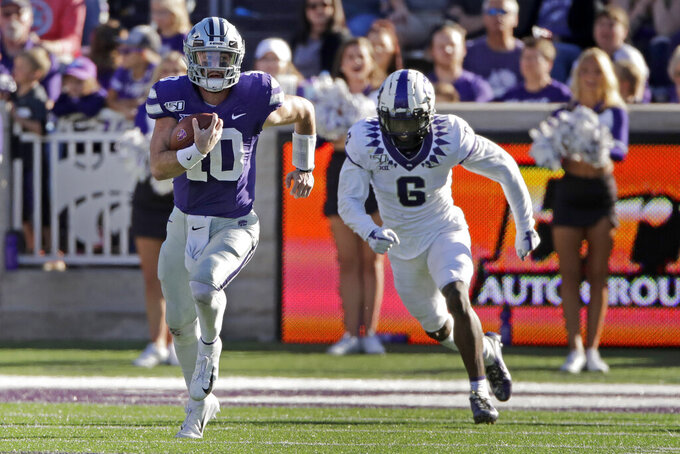 Kansas State quarterback Skylar Thompson (10) is chased by TCU safety Innis Gaines (6) as he runs for a first down during the second half of an NCAA college football game Saturday, Oct. 19, 2019, in Manhattan, Kan. Kansas State won 24-17. (AP Photo/Charlie Riedel)