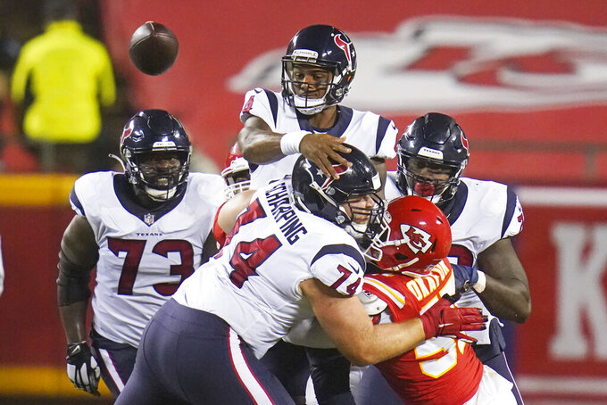 Houston Texans quarterback Deshaun Watson, top, gets a pass away behind the blocking of offensive tackle Max Scharping (74) in the first half of an NFL football game against the Kansas City Chiefs Thursday, Sept. 10, 2020, in Kansas City, Mo. (AP Photo/Jeff Roberson)