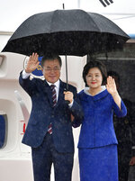 South Korean President Moon Jae-in, left, and his wife Kim Jung-sook arrive at Kansai International Airport in Izumisano, Osaka prefecture, western Japan, Thursday, June 27, 2019. Group of 20 leaders gather in Osaka on June 28 and 29 for their annual summit.(Nobuki Ito/Kyodo News via AP)