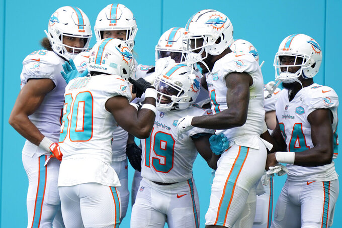 Teammates congratulate Miami Dolphins wide receiver Jakeem Grant (19) after Grant scored a touchdown, during the first half of an NFL football game against the Los Angeles Rams, Sunday, Nov. 1, 2020, in Miami Gardens, Fla. (AP Photo/Wilfredo Lee)