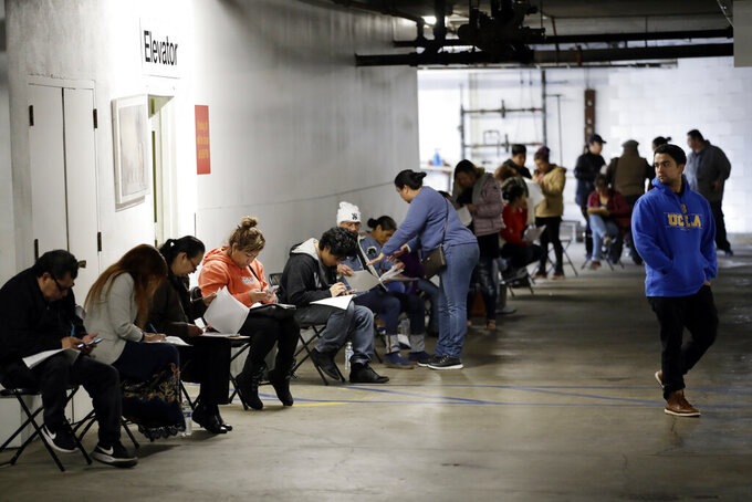 FILE - In this March 13, 2020 file photo, unionized hospitality workers wait in line in a basement garage to apply for unemployment benefits at the Hospitality Training Academy in Los Angeles.  More than 6.6 million Americans applied for unemployment benefits last week, far exceeding a record high set just last week, a sign that layoffs are accelerating in the midst of the coronavirus.   (AP Photo/Marcio Jose Sanchez, File)