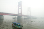 A boat motors through thick haze from forest fires blanket Ampera Bridge in the background in Palembang, South Sumatra, Indonesia, Monday, Oct. 14, 2019. Thick, noxious haze from new deliberately set fires blanketed parts of Indonesia's Sumatra island on Monday after days of improving air quality, causing school closings and flight delays. (AP Photo/Iwan Cheristian)