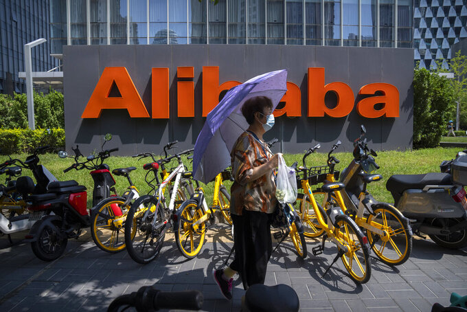 A woman holds an umbrella as she walks past the offices of Chinese e-commerce firm Alibaba in Beijing on Aug. 10, 2021. China is tightening control over data gathered by companies about the public under a law approved Friday, Aug. 20, 2021 by its ceremonial legislature, expanding the ruling Communist Party's crackdown on internet industries. The data protection law follows anti-monopoly and other enforcement actions against companies including e-commerce giant Alibaba and games and social media operator Tencent that caused their share prices to plunge. (AP Photo/Mark Schiefelbein)