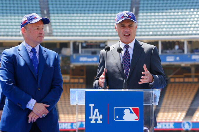 FILE - In this April 11, 2018, file photo, Los Angeles President and CEO Stan Kasten, left, and Baseball Commissioner Rob Manfred announce that Dodger Stadium will host the All-Star Game in 2020 for the first time since 1980 at a news conference in Los Angeles. Dodger Stadium's 40-year wait to host the All-Star Game is going to last even longer. The game scheduled for July 14 was canceled Friday, July 3, 2020, because of the coronavirus pandemic, and Dodger Stadium was awarded the 2022 Midsummer Classic. (AP Photo/Damian Dovarganes, File)