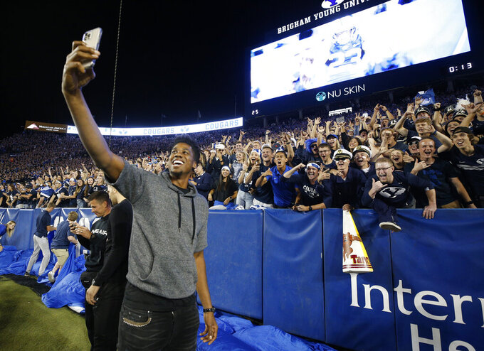 NBA Utah Jazz center Hassan Whiteside take a selfie picture with BYU fans in the first half of an NCAA college football game against South Florida Saturday, Sept. 25, 2021, in Provo, Utah. (AP Photo/George Frey)