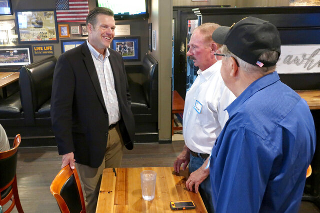 Kris Kobach, left, a Republican candidate for the U.S. Senate in Kansas, speaks with supporters Bill Vonderschmidt, center, and Bob Sines, both from Hiawatha, Kan., Wednesday, July 29, 2020, during a meet-and-greet event in Holton, Kan. Kobach is locked in a tight race with western Kansas Rep. Roger Marshall for the GOP nomination. (AP Photo/John Hanna)