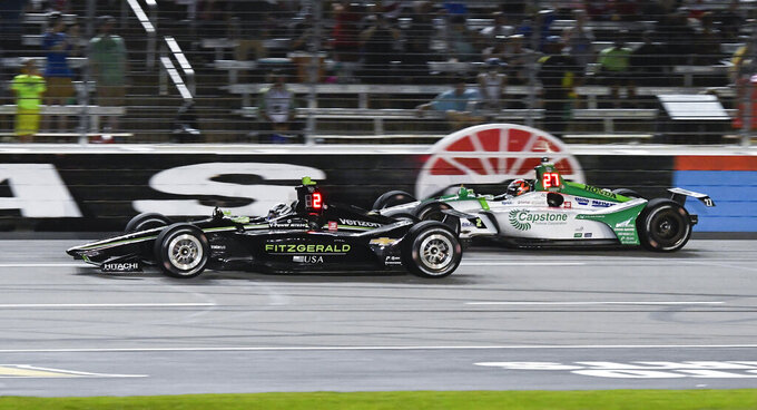 Josef Newgarden (2) leads Alexander Rossi (27) during the IndyCar auto race at Texas Motor Speedway, Saturday, June 8, 2019, in Fort Worth, Texas. Newgarden won the race. (AP Photo/Larry Papke)