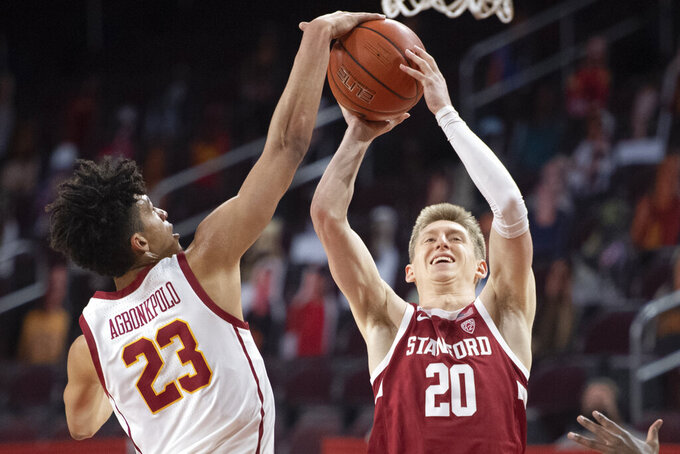 Southern California forward Max Agbonkpolo, left, blocks the shot by Stanford guard Noah Taitz during the first half of an NCAA college basketball game Wednesday, March 3, 2021, in Los Angeles. (AP Photo/Kyusung Gong)