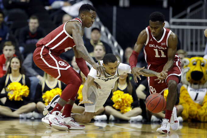 Missouri guard Xavier Pinson, center, dives for a loose ball between Oklahoma forward Kristian Doolittle, left, and guard De'Vion Harmon (11) during the first half of an NCAA college basketball game, Tuesday, Nov. 26, 2019, in Kansas City, Mo. (AP Photo/Charlie Riedel)