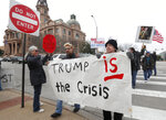 Carolyn Hursh, right, and Joey Daniel, carry a sign during a protest with others in downtown Fort Worth, Texas, Monday, Feb. 18, 2019. People gathered on the Presidents Day holiday to protest President Donald Trump's recent national emergency declaration. (AP Photo/LM Otero)