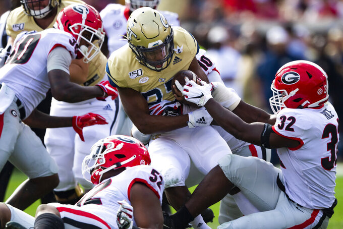 FILE - In this Nov. 30, 2019, file photo, Georgia Tech running back Jordan Mason (27) tries to evade a tackle as Georgia linebacker Monty Rice (32) holds on during the first half of an NCAA college football game in Atlanta. The Southeastern Conference's conference-only scheduling decision during the coronavirus pandemic wiped out any hopes of saving four in-state rivalries against Atlantic Coast Conference opponents, all traditionally played on the final Saturday of the regular season. (AP Photo/John Amis, File)