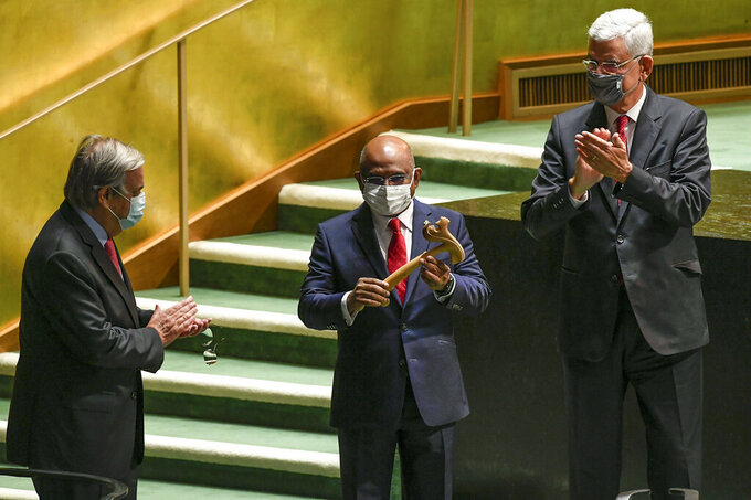 FILE - In this Tuesday, Tuesday, Sept. 14, 2021, file photo provided by United Nations, U.N. Secretary-General António Guterres, left, and Volkan Bozkir, right, president of the 75th session of the United Nations General Assembly, applaud as Abdulla Shahid, center, receives the gavel as the new president of the 76th session of the UNGA at U.N. headquarters. World leaders will have to be vaccinated against the coronavirus to speak at the U.N. General Assembly's big meeting next week, the assembly leader and New York City officials said this week, prompting swift objections from at least one nation.(Evan Schneider/United Nations Photo via AP, File)