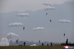 "This undated photo provided on Monday, Nov. 18, 2019, by the North Korean government shows a parachuting drill of military sharpshooters at an unknown location in North Korea. North Korean leader Kim Jong Un supervised a parachuting drill of military sharpshooters and vowed to build an ""invincible army,"" displaying more defiance even as the United States and South Korea called off their own exercises to create space for nuclear diplomacy. Independent journalists were not given access to cover the event depicted in this image distributed by the North Korean government. The content of this image is as provided and cannot be independently verified. Korean language watermark on image as provided by source reads:"