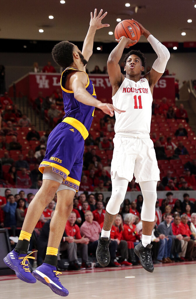Houston guard Nate Hinton (11) puts up a three point shot as East Carolina guard K.J. Davis, left, defends during the first half of an NCAA college basketball game Wednesday, Jan. 23, 2019, in Houston. (AP Photo/Michael Wyke)