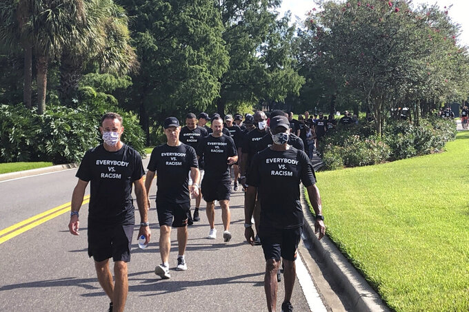 NBA referees march in support of players seeking an end to racial injustice in Lake Buena Vista, Fla., Thursday, Aug. 27, 2020. Their march came shortly before players met to decide on restarting the season after three games were postponed Wednesday.  (AP Photo/Brian Mahoney)