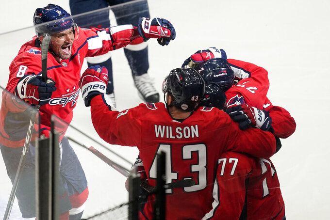 CORRECTS THAT GOAL WAS SCORED BY NIC DOWD, INSTEAD OF T.J. OSHIE - Washington Capitals left wing Alex Ovechkin (8) comes in to celebrate with right wing Tom Wilson (43), right wing T.J. Oshie (77) and defenseman Justin Schultz (2) after Nic Dowd's overtime goal on a deflection of a shot by Oshie in Game 1 of an NHL hockey Stanley Cup first-round playoff series against the Boston Bruins, Saturday, May 15, 2021, in Washington. The Capitals won 3-2. (AP Photo/Alex Brandon)