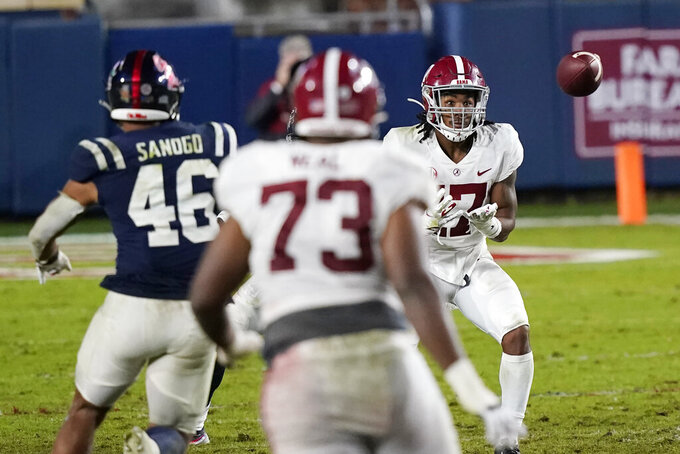 Alabama wide receiver Jaylen Waddle (17) keeps his eyes on a pass as Mississippi linebacker MoMo Sanogo (46) closes in for a tackle during the second half of an NCAA college football game in Oxford, Miss., Saturday, Oct. 10, 2020. Alabama won 63-48. (AP Photo/Rogelio V. Solis)