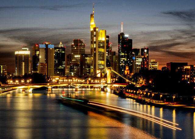 Long time exposure photo shows a cargo ship on the river Main with the buildings of the banking district in background in Frankfurt, Germany, Sunday, Sept. 20, 2020. (AP Photo/Michael Probst)