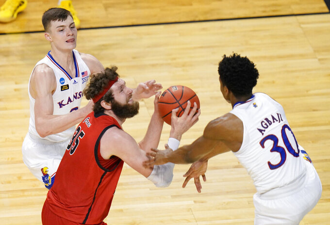 FILE - In this March 20, 2021, file photo, Eastern Washington forward Tanner Groves (35) is pressured by Kansas guards Christian Braun, left, and Ochai Agbaji (30) during the second half of a first-round game in the NCAA men's college basketball tournament in Indianapolis. Groves, now at Oklahoma, was the 2021 Big Sky Conference Player of the Year for Eastern Washington last year. He averaged 17.2 points and 8.0 rebounds while shooting 56.0% from the field as a junior last season. (AP Photo/AJ Mast, File)