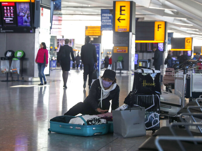 A woman wearing a face mask packs her suitcase in the departures area of Terminal 5, after it was announced British Airways has suspended all services to and from China, at London's Heathrow Airport, Wednesday, Jan. 29, 2020. British Airways and Asian budget carriers Lion Air and Seoul Air are among the airlines suspending flights to China as fears of a new virus that has killed more than 130 people spread. Several other airlines including Finnair, Hong Kong-based Cathay Pacific and Singapore-based Jetstar Asia are reducing the number of flights to the country as demand for travel drops because of the outbreak.  (Steve Parsons/PA via AP)