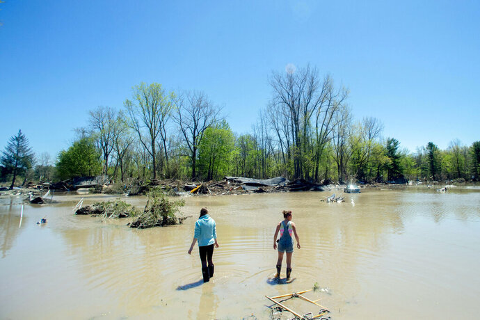 Kendra Tucker, left, and her sister Melissa McCann, both of Sanford, wade into flood waters as they work to uncover lost family heirlooms and belongings, Thursday, May 21, 2020, in Sanford, Mich. Scores of displaced people are staying in shelters after flooding overwhelmed two dams, submerged homes and washed out roads in Central Michigan. (Jake May/MLive.com/The Flint Journal via AP)