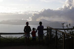 People watch from Tagaytay, Cavite province, south of Manila, as Taal Volcano continues to spew ash on Tuesday, Jan. 14, 2020. Thousands of people fled the area through heavy ash as experts warned that the eruption could get worse and plans were being made to evacuate more.(AP Photo/Aaron Favila)