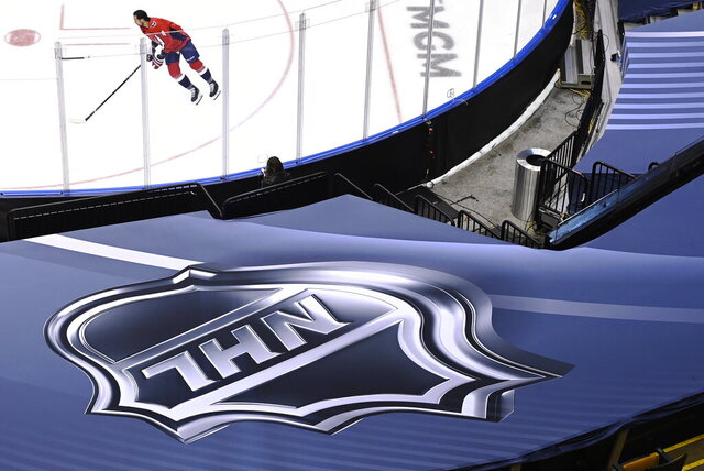 An NHL logo is shown as Washington Capitals defenseman Brenden Dillon (4) skates prior to NHL Eastern Conference Stanley Cup playoff hockey action against the New York Islanders in Toronto, Friday, Aug. 14, 2020. The NHL is providing its playoff teams a few tastes of home in their respective hub cities. Teams are hearing their pre-game warm-up music, goal songs and national anthem performers. Crowd noise is being piped in and new camera angles have been added for a TV audience. (Nathan Denette/The Canadian Press via AP)