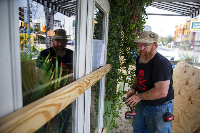 Dylan Blackthorn boards up Hillside Farmacy restaurant right before the Texas Gov. Greg Abbott bans gatherings, shuts down restaurants, bars, schools on Thursday, March 19, 2020. (Ricardo B. Brazziell/Austin American-Statesman via AP)