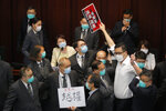 Pro-establishment politician, Starry Lee, center, speaks as pan-democratic legislator Lam Cheuk-ting, right, scuffles with security guards during a Legislative Council's House Committee meeting, in Hong Kong, Friday, May 8, 2020. Scuffles also broke out when Lee called the meeting to order, with pro-democracy lawmakers rushing the table as security shoved back. Security guards physically carried out pro-democracy lawmakers Chu Hoi Dick and Ray Chan, who were ordered to leave due to disorderly conduct. (AP Photo/Kin Cheung)
