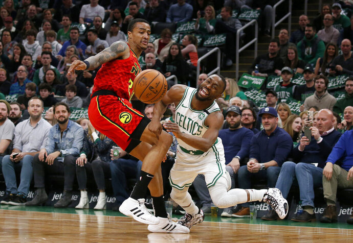 Boston Celtics guard Kemba Walker, right, reacts as he is fouled by Atlanta Hawks forward John Collins during the first half of an NBA basketball game Friday, Feb. 7, 2020, in Boston. (AP Photo/Mary Schwalm)