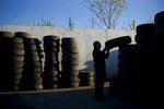 FILE- In this Thursday, Nov. 19, 2015, file photo, junkyard employee Fabio Flores stacks up used tires at Aadlen Brothers Auto Wrecking, also known as U Pick Parts, in the Sun Valley section of Los Angeles. California may ask tire manufacturers to look at ways of eliminating zinc from their products because studies have shown the mineral may harm aquatic wildlife when it is washed into rivers and lakes. (AP Photo/Jae C. Hong, File)