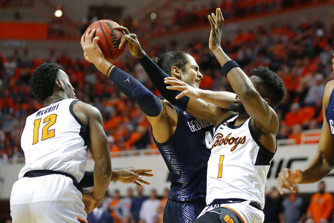 Georgetown's Omer Yurtseven (44) reaches for the ball between Oklahoma State's Cameron McGriff (12) and Jonathan Laurent (1) during an NCAA college basketball game in Stillwater, Okla., Wednesday, Dec. 4, 2019. (Bryan Terry/The Oklahoman via AP)