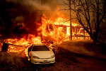 Flames from the Dixie Fire consume a home on Highway 89 south of Greenville on Thursday, Aug. 5, 2021, in Plumas County, Calif. (AP Photo/Noah Berger)
