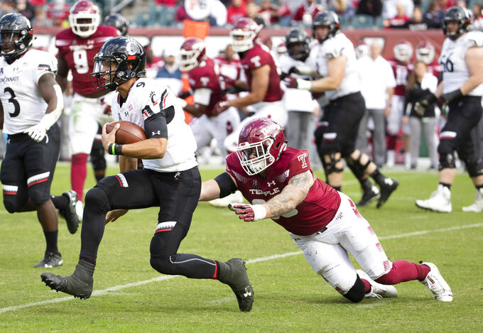Cincinnati's quarterback Desmond Ridder (9) scrambles past Temple's defensive end Jimmy Hogan (98) during the second half of an NCAA college football, Saturday, Oct. 20, 2018, in Philadelphia. Temple won 24-17 in overtime. (AP Photo/Chris Szagola)