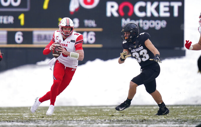 Utah quarterback Jake Bentley, left, is pursued by Colorado linebacker Joshka Gustav in the first half of an NCAA college football game Saturday, Dec. 12, 2020, in Boulder, Colo. (AP Photo/David Zalubowski)
