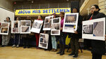 In this March 7, 2019 photo, residents of the Jacob Riis Settlement at the Queensbridge Houses, the largest public housing project in New York City, hold enlarged photographs of damages to their apartments caused by leaks, mold, peeling paint and other issues during a community town hall meeting in New York with HUD executive Lynne Patton. Patton spent a month living in and touring some of the city's public housing projects to discover first-hand persistent problems in the city's public housing projects. (AP Photo/Kathy Willens)