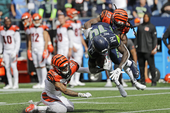 Seattle Seahawks wide receiver DK Metcalf (14) is tackled by Cincinnati Bengals cornerback B.W. Webb (23) and free safety Jessie Bates (30) after Metcalf made a catch during the second half of an NFL football game Sunday, Sept. 8, 2019, in Seattle. (AP Photo/John Froschauer)