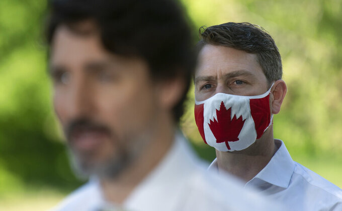 In this photo taken on June 19, 2020, Liberal Member of Parliament William Amos wears a Canadian flag mask as Prime Minister Justin Trudeau speaks during a news conference in Chelsea, Quebec. Amos, who has represented the Quebec district of Pontiac since 2015, appeared on the screens of his fellow lawmakers completely naked on Wednesday, April 14, 2021. He has apologized to his colleagues and says his video was accidentally turned on as he was changing into his work clothes after going for a jog. (Adrian Wyld/The Canadian Press via AP)
