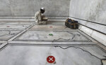 An Indian Muslim offers prayers on the eve of Eid al-Adha with social distancing marking on the floor at Jama Masjid in New Delhi, India, Friday, July 31, 2020. Eid al-Adha, or the Feast of the Sacrifice, is marked by sacrificing animals to commemorate the prophet Ibrahim's faith in being willing to sacrifice his son. (AP Photo/Manish Swarup)