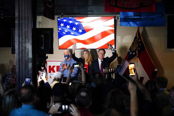 Sen. Rick Scott, R-Fla., left, Republican candidates for U.S. Senate Sen. Kelly Loeffler, center, and Sen. David Perdue wave to a crowd during a campaign rally on Friday, Nov. 13, 2020, in Cumming, Ga. (AP Photo/Brynn Anderson)