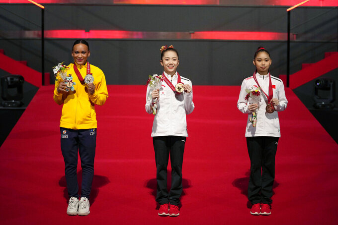 Wei Xiaoyuan, center, of China, with her gold medal, Rebeca Andrade, left, of Brazil, with her silver medal, and Luo Rui, of China, pose for photos and video during the victory ceremony for the women's uneven bars final in the FIG Artistic Gymnastics World Championships in Kitakyushu, western Japan, Saturday, Oct. 23, 2021. (AP Photo/Hiro Komae)